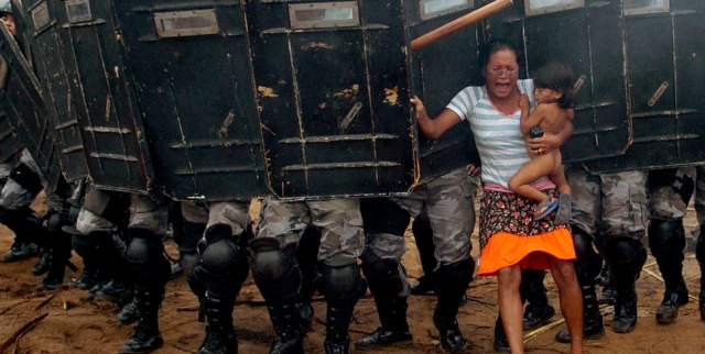 An indigenous woman holds her child while trying to resist the advance of Amazonas state policemen in Manaus who have been sent to evict natives. [2008]
