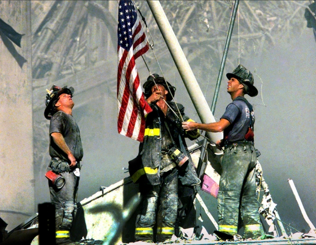 Firefighters raise the American flag on the ruins on the World Trade Centers [2001]